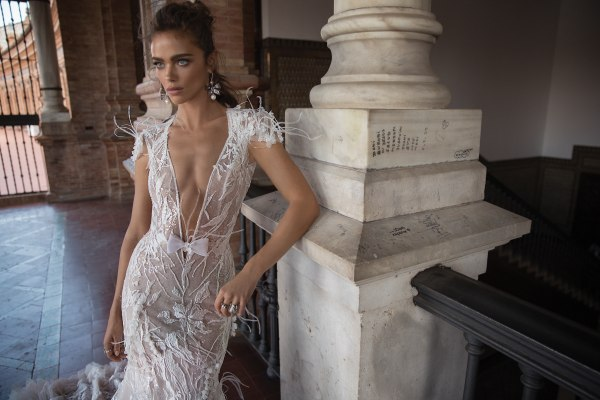Sheer trumpet wedding dress with floral appliques and plunging neckline